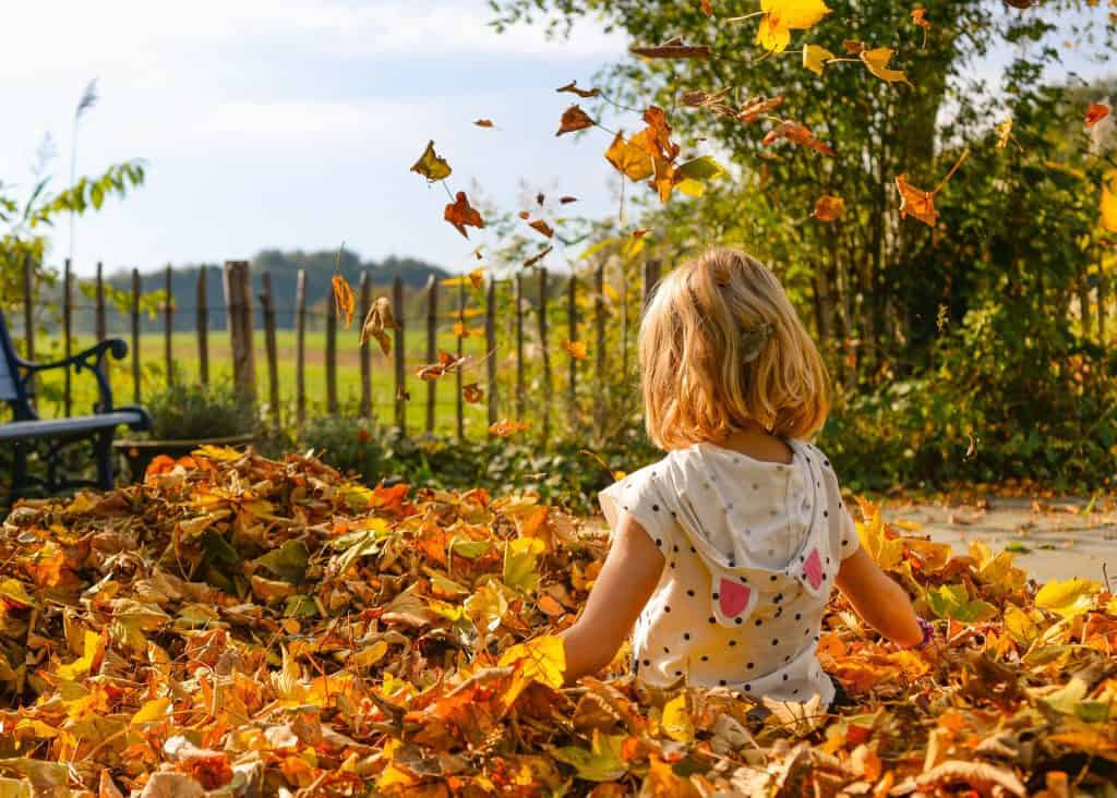 Girl playing with leafs outdoor